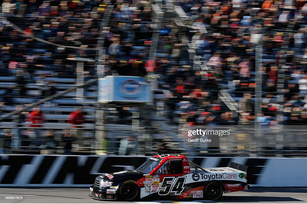 Darrell Wallace Jr., driver of the #54 ToyotaCare Toyota, crosses the finish line to win the NASCAR Camping World Truck Series Kroger 200 at Martinsville Speedway on October 26, 2013 in Martinsville, Virginia.