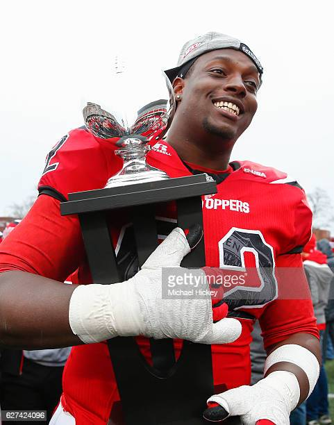 Darrell Williams Jr #62 of the Western Kentucky Hilltoppers carries the championship trophy off the field following the CUSA Championship game...