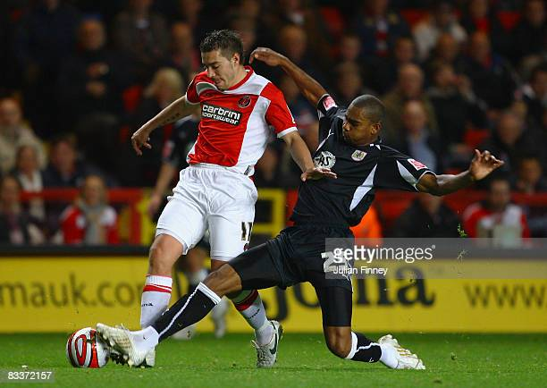 Darren Ambrose of Charlton is tackled by Marvin Elliott of Bristol City during the Coca Cola Championship match between Charlton Athletic and Bristol...
