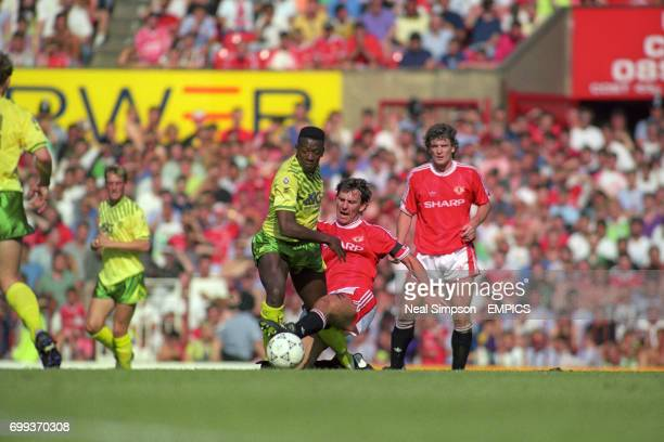 Darren Beckford Norwich City overcomes the sliding tackle from Manchester United's Bryan Robson