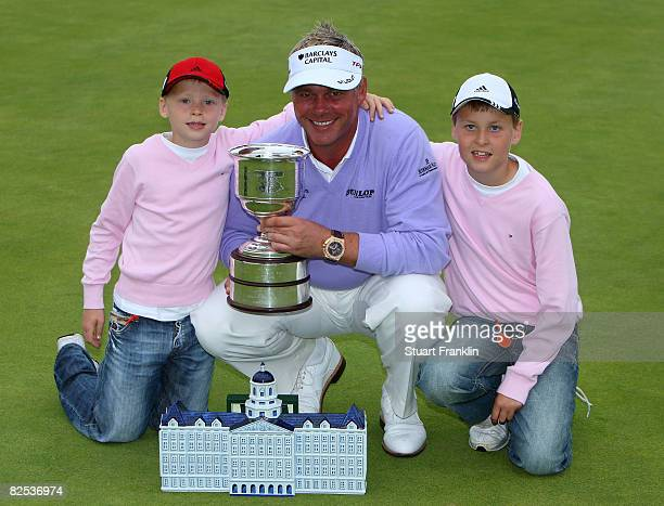 Darren Clarke of Northern Ireland celebrates with his sons Conor Clarke and Tyrone Clarke as he holds the trophy for winning The KLM Open at Kennemer...