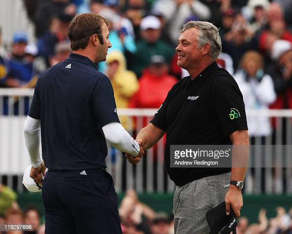 Darren Clarke of Northern Ireland shakes hands with Dustin Johnson of the United States after his victory on the 18th green during the final round of...