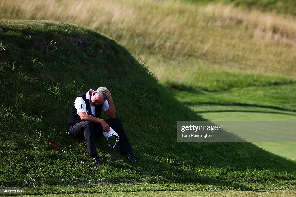 Darren Clarke of Northern Ireland sits in the grass on the 17th hole during the first round of the 2015 PGA Championship at Whistling Straits on August 13, 2015 in Sheboygan, Wisconsin.
