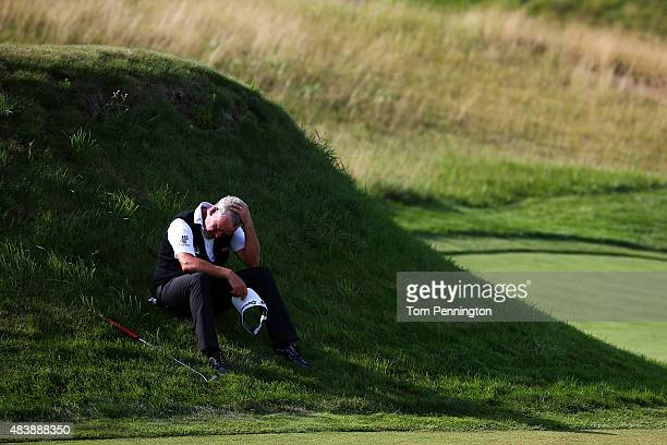 Darren Clarke of Northern Ireland sits in the grass on the 17th hole during the first round of the 2015 PGA Championship at Whistling Straits on...