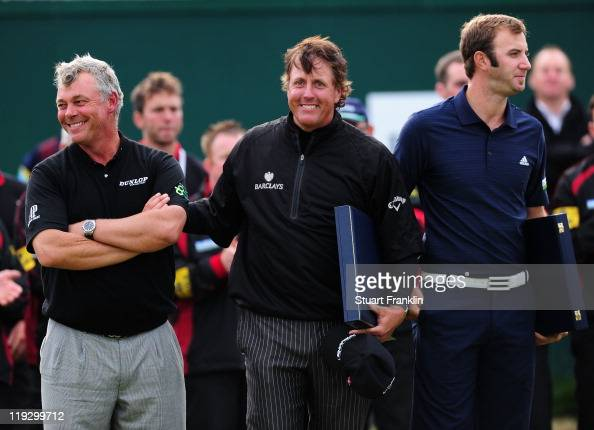 Darren Clarke of Northern Ireland stands with Phil Mickelson and Dustin Johnson of the United States following his victory on the 18th green during...