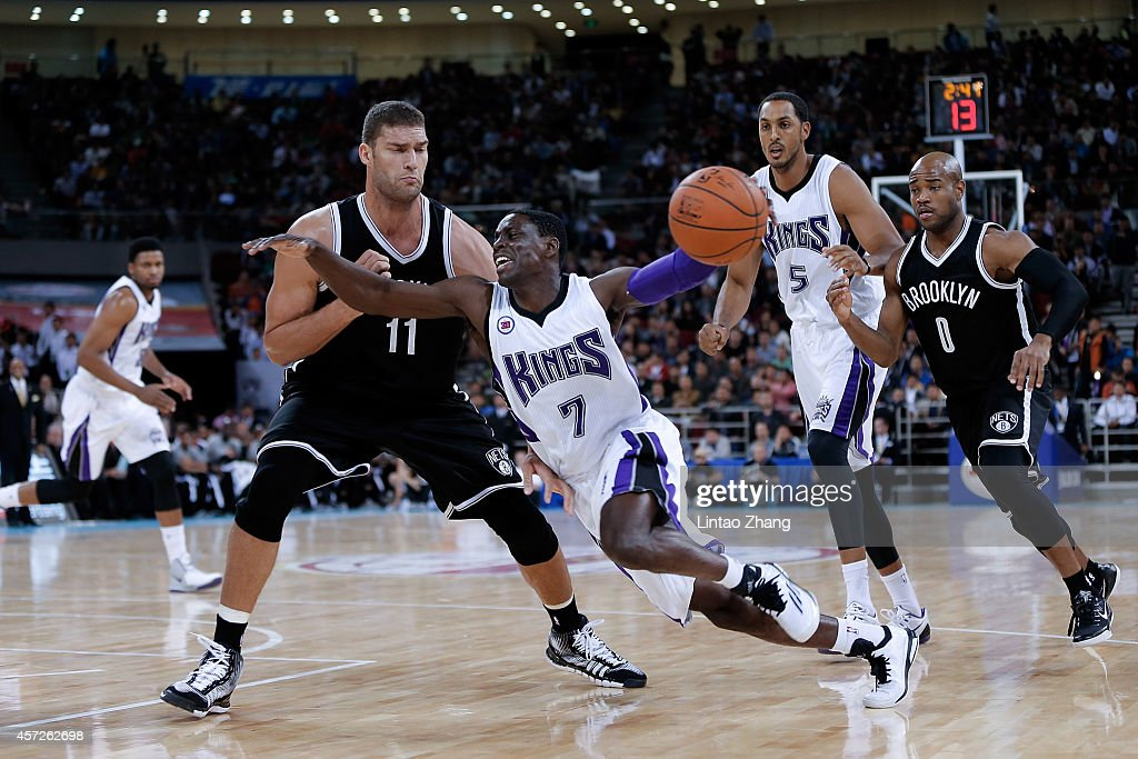 Darren Collison of Sacramento Kings drives against Brook Lopez of Brooklyn Nets during the 2014 NBA Global Games match between the Brooklyn Nets and...