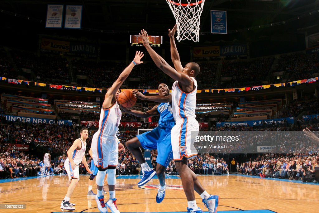 Darren Collison #4 of the Dallas Mavericks drives to the basket against Serge Ibaka #9 and Russell Westbrook #0 of the Oklahoma City Thunder on December 27, 2012 at the Chesapeake Energy Arena in Oklahoma City, Oklahoma.