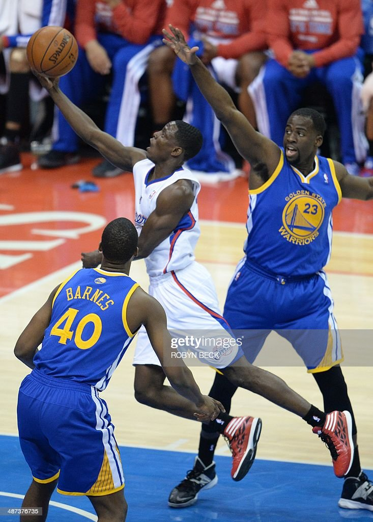 Darren Collison (C) of the Los Angeles Clippers shots before Harrison Barnes (L) and Draymond Green (R) of the Golden State Warriors during Game 5 of their first-round NBA playoff game April 29, 2014 at Staples Center in Los Angeles, California. The NBA banned Clippers owner Donald Sterling from professional basketball for life over racist comments that the league's commissioner dubbed 'deeply offensive and harmful.' AFP PHOTO / ROBYN BECK