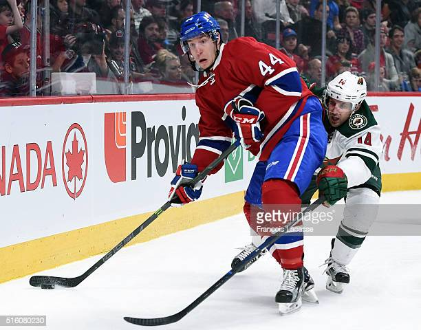 Darren Dietz of the Montreal Canadiens looks to pass the puck against Justin Fontaine against the Minnesota Wild in the NHL game at the Bell Centre...
