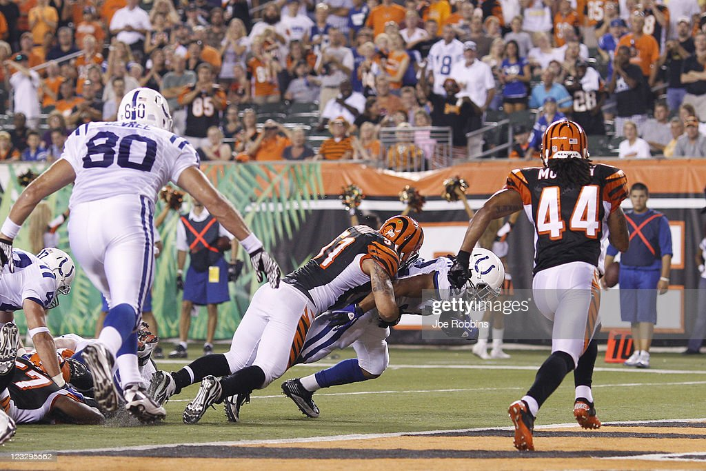 Darren Evans #32 of the Indianapolis Colts runs into the end zone for a one-yard touchdown in the fourth quarter through the grasp of Dan Skuta #51 of the Cincinnati Bengals during an NFL preseason game against at Paul Brown Stadium on September 1, 2011 in Cincinnati, Ohio. The Colts won 17-13.