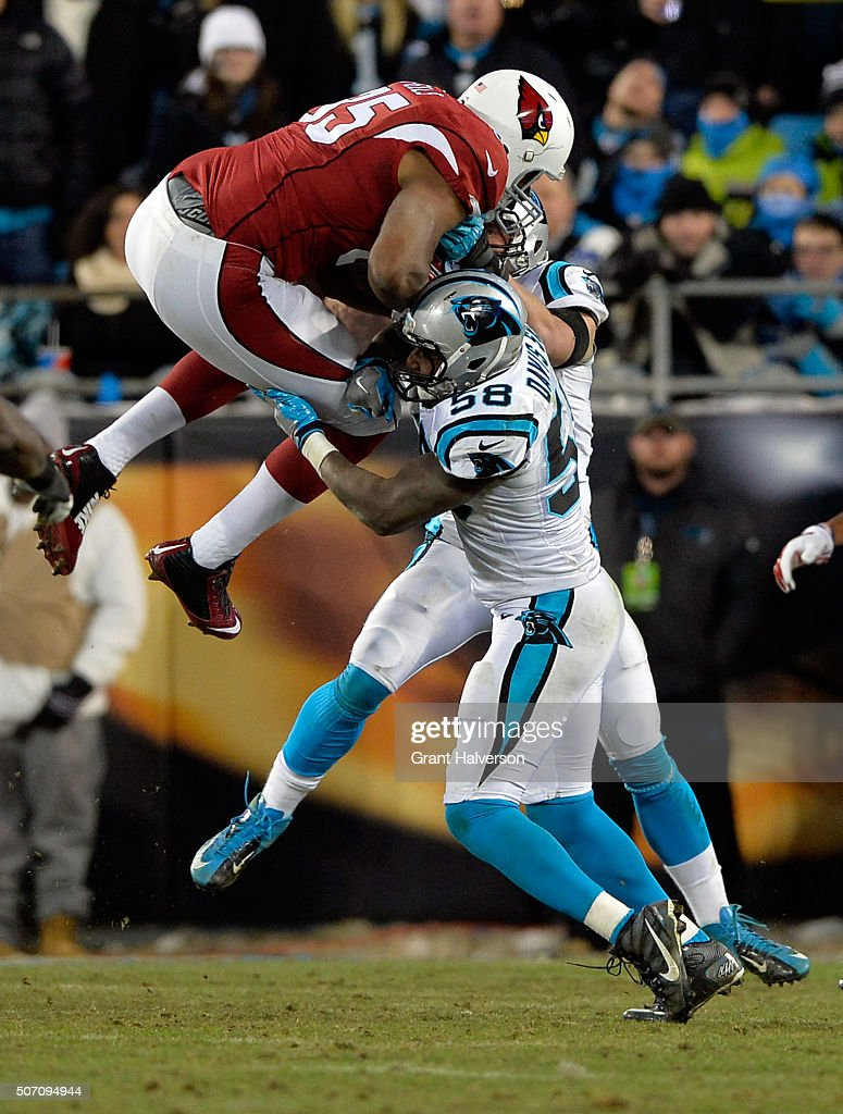 Darren Fells of the Arizona Cardinals collides with Thomas Davis and Luke Kuechly of the Carolina Panthers during the NFC Championship Game at Bank...