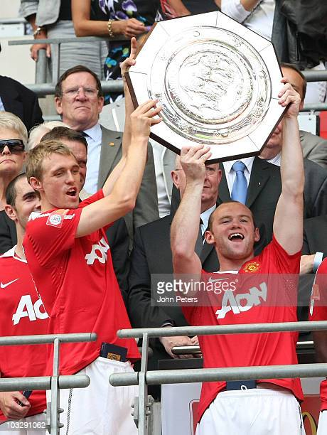 Darren Fletcher and Wayne Rooney of Manchester United hold aloft the Community Shield trophy after the FA Community Shield match between Chelsea and...