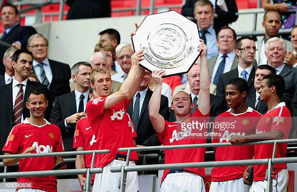 Darren Fletcher and Wayne Rooney of Manchester United lift the trophy and celebrate with team mates after victory in the FA Community Shield match...
