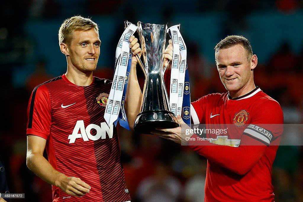 Darren Fletcher #24 of Manchester United and (R) Wayne Rooney #10 of Manchester United lift the winners trophy following their 3-1 victory over Liverpool in the Guinness International Champions Cup 2014 Final at Sun Life Stadium on August 4, 2014 in Miami Gardens, Florida.