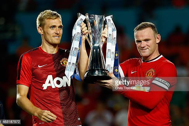 Darren Fletcher of Manchester United and Wayne Rooney of Manchester United lift the winners trophy following their 31 victory over Liverpool in the...
