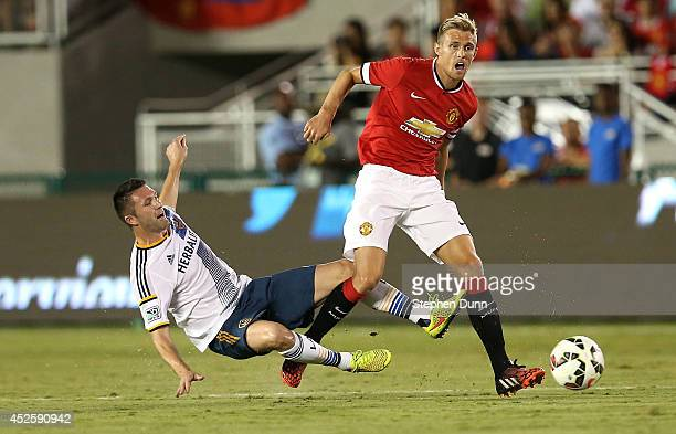 Darren Fletcher of Manchester United fights for the ball against the tackle of Robbie Keane of the Los Angeles Galaxy at the Rose Bowl on July 23...