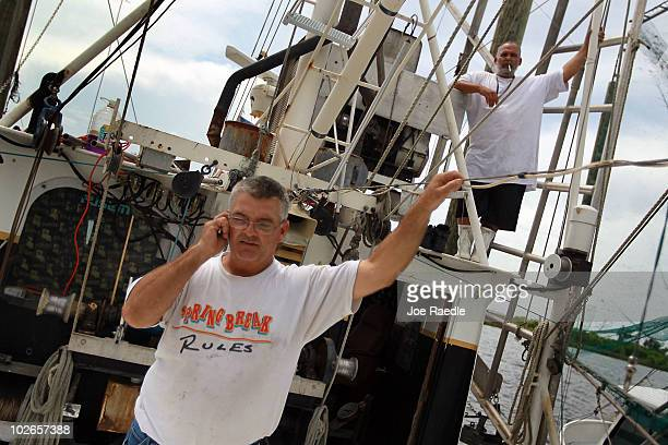 Darren Frickey talks on his cell phone as he prepares to get his shrimping boat underway at Rigolets marina on July 6 2010 in Greens Ditch Louisiana...