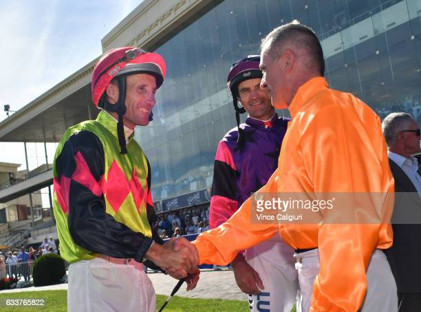 Darren Gauci is congratulated by Damien Oliver during a guard of honour from his family friends and fellow jockeys before his last career ride in...