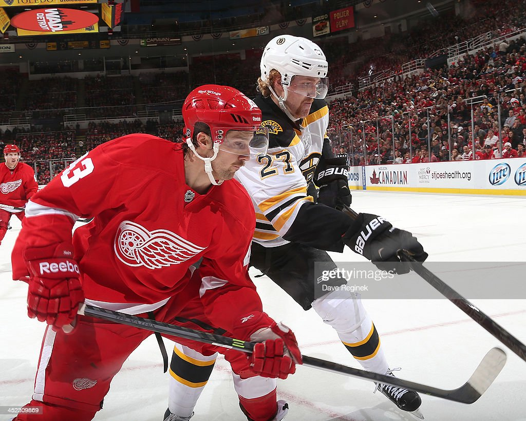 <a gi-track='captionPersonalityLinkClicked' href=/galleries/search?phrase=Darren+Helm&family=editorial&specificpeople=3949334 ng-click='$event.stopPropagation()'>Darren Helm</a> #43 of the Detroit Red Wings and <a gi-track='captionPersonalityLinkClicked' href=/galleries/search?phrase=Dougie+Hamilton&family=editorial&specificpeople=6686524 ng-click='$event.stopPropagation()'>Dougie Hamilton</a> #27 of the Boston Bruins go hard into the corner during an NHL game at Joe Louis Arena on November 27, 2013 in Detroit, Michigan. Detroit defeated Boston 6-1