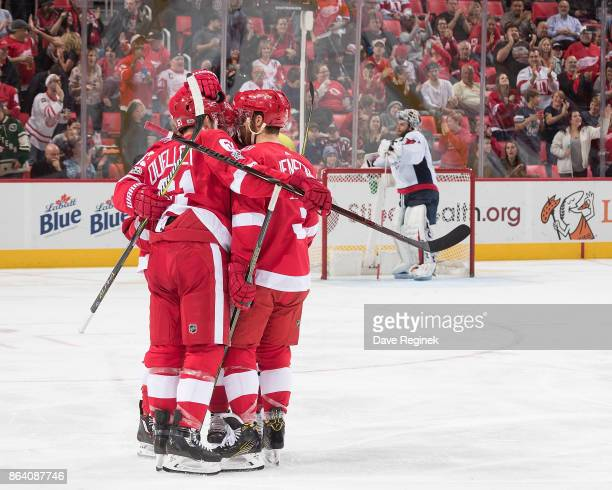 Darren Helm of the Detroit Red Wings celebrates his unassisted second period goal with teammates Xavier Ouellet and Nick Jensen in front of...