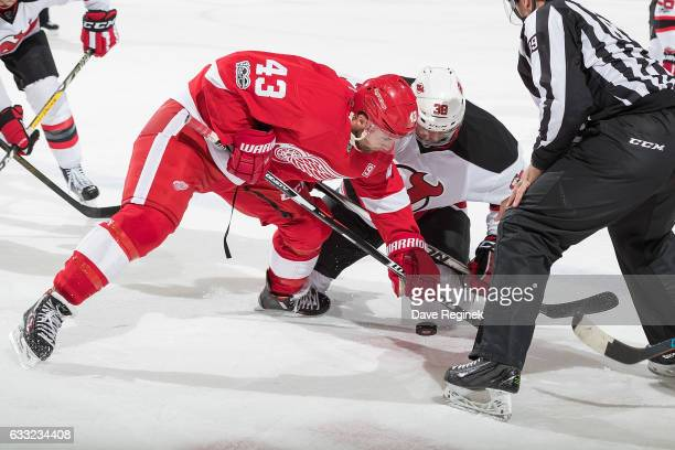 Darren Helm of the Detroit Red Wings faces off against Vernon Fiddler of the New Jersey Devils during an NHL game at Joe Louis Arena on January 31...