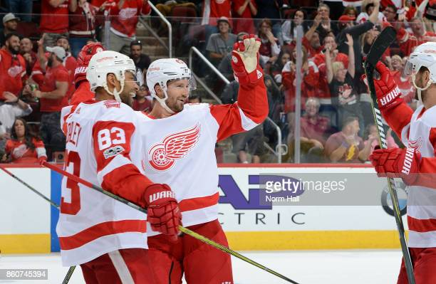 Darren Helm of the Detroit Red Wings is congratulated by Trevor Daley and teammates after his assist on a goal against the Arizona Coyotes during the...