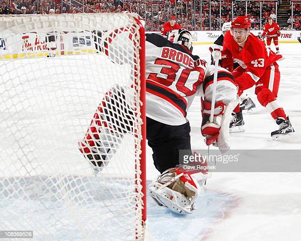 Darren Helm of the Detroit Red Wings scores a goal on Martin Brodeur of the New Jersey Devils during an NHL game at Joe Louis Arena on January 26...