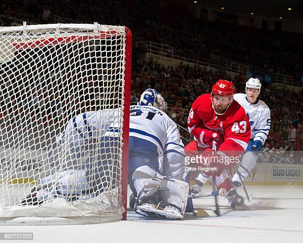 Darren Helm of the Detroit Red Wings skates in with the puck looking to score on Frederik Andersen of the Toronto Maple Leafs as Jake Gardiner of the...