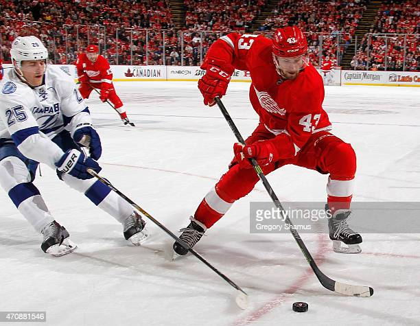 Darren Helm of the Detroit Red Wings tries to avoid the stick of Matt Carle of the Tampa Bay Lightning during the second period of Game Four of the...