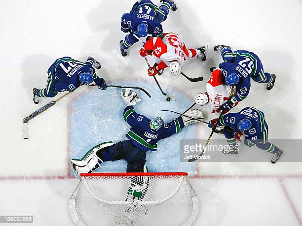 Darren Helm of the Detroit Red Wings tries to take a shot at a stickless Roberto Luongo of the Vancouver Canucks during their NHL game at Roger s...