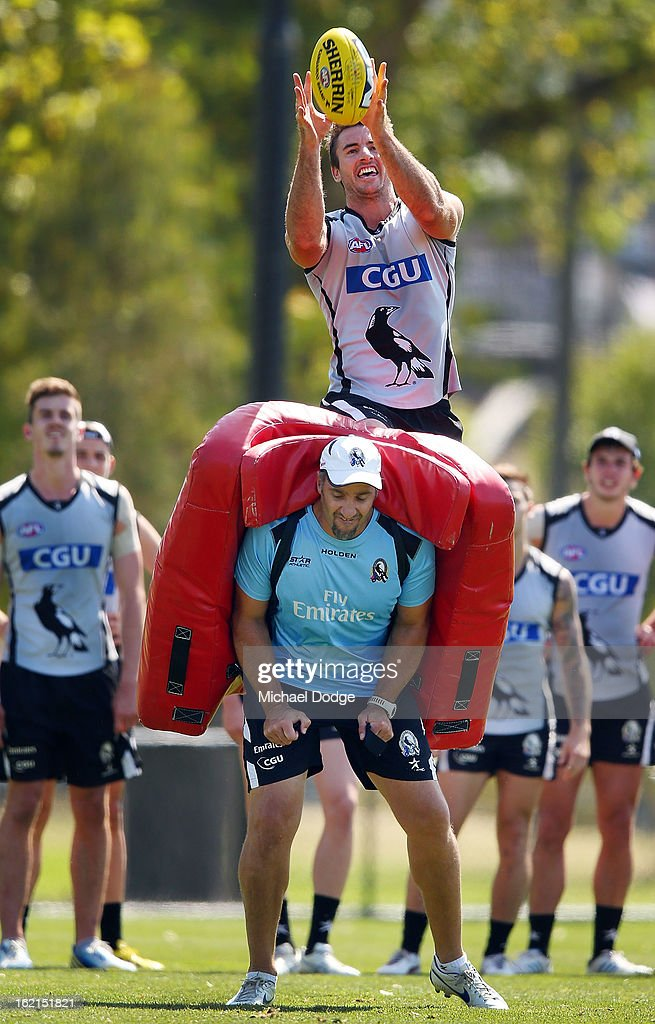 Darren Jolly takes a mark over assistant coach Anthony Rocca during a Collingwood Magpies AFL training session at Gosch's Paddock on February 20, 2013 in Melbourne, Australia.