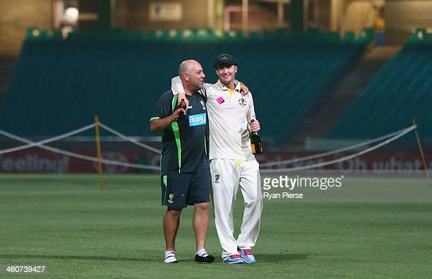 Darren Lehmann coach of Australia and Michael Clarke of Australia talk on the pitch at midnight after day three of the Fifth Ashes Test match between...