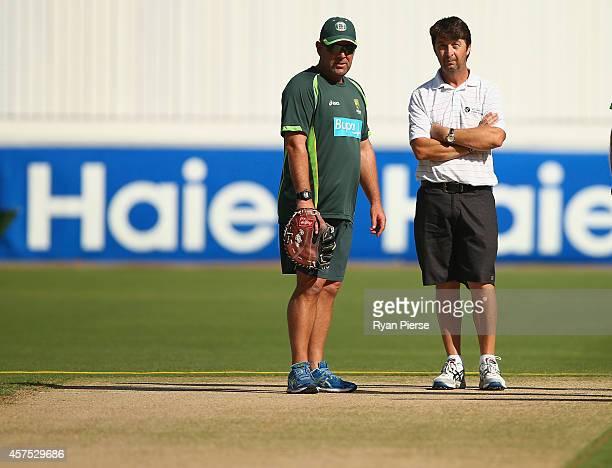 Darren Lehmann coach of Australia and Tony Hemming Head Curator inspect the pitch during an Australian Nets Session at Dubai International Stadium on...