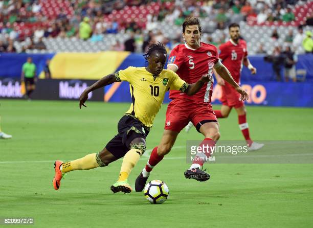 Darren Mattocks of Jamaica brings the ball up field while being defended by Dejan Jakovic of Canada in a quarterfinal match during the CONCACAF Gold...