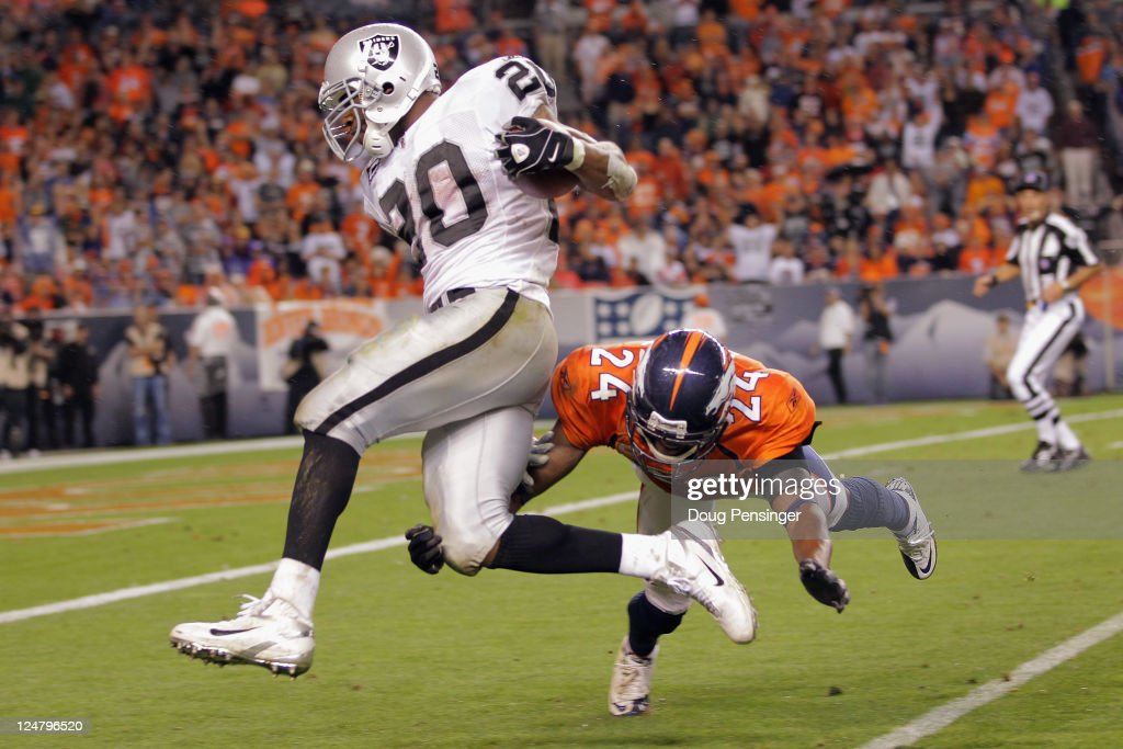 Darren McFadden #20 of the Oakland Raiders is tackled by Champ Bailey #24 of the Denver Broncos at the one yard line after rushing for 47 yards to set up a fourth quarter touchdown at Sports Authority Field at Mile High on September 12, 2011 in Denver, Colorado. The Raiders defeated the Broncos 23-20.