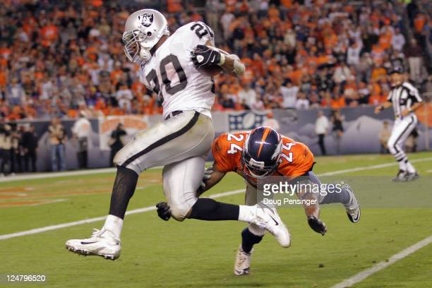 Darren McFadden of the Oakland Raiders is tackled by Champ Bailey of the Denver Broncos at the one yard line after rushing for 47 yards to set up a...