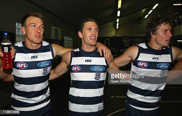 Darren Milburn Joel Selwood and Mitch Duncan of the Cats sing the song in the rooms after winning the round seven AFL match between the Geelong Cats...