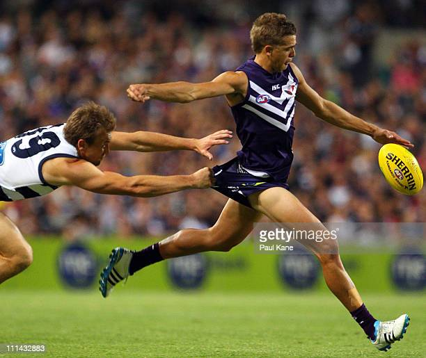 Darren Milburn of the Cats attempts to tackle Stephen Hill of the Dockers during the round two AFL match between the Fremantle Dockers and the...