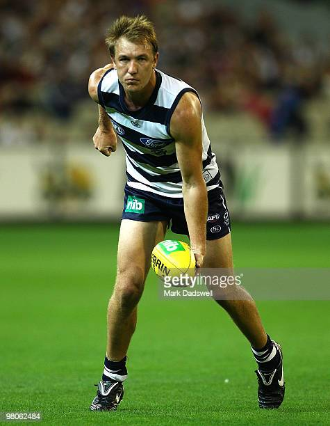 Darren Milburn of the Cats handballs during the round one AFL match between the Geelong Cats and the Essendon Bombers at Melbourne Cricket Ground on...