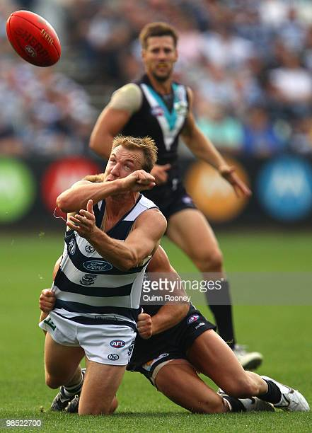 Darren Milburn of the Cats handballs whilst being tackled during the round four AFL match between the Geelong Cats and the Port Adelaide Power at...