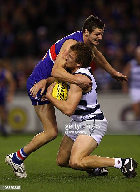 Darren Milburn of the Cats is tackled high by Andrejs Everitt of the Bulldogs during the round 20 AFL match between the Western Bulldogs and the...