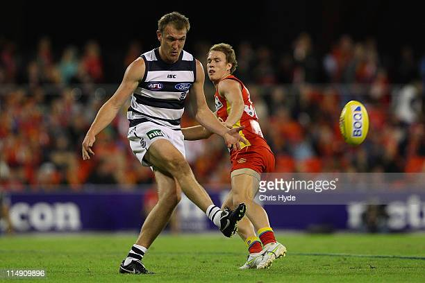Darren Milburn of the Cats kicks during the round 10 AFL match between the Gold Coast Suns and Geelong Cats at Metricon Stadium on May 28 2011 in...