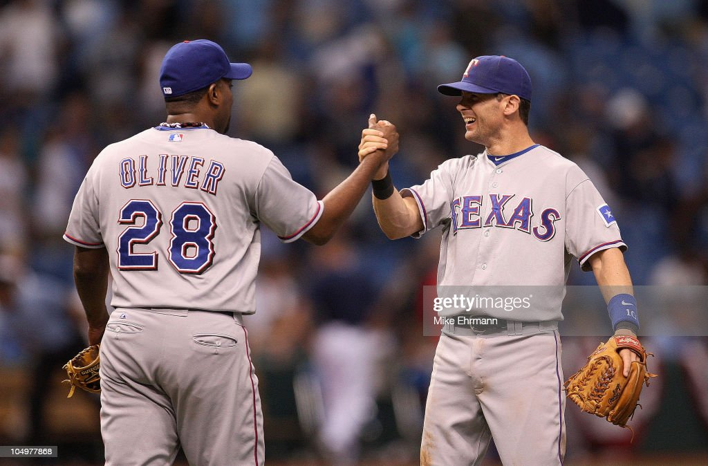 Darren Oliver of the Texas Rangers is congratulated by Michael Young after winning Game 2 of the ALDS against the Tampa Bay Rays at Tropicana Field...