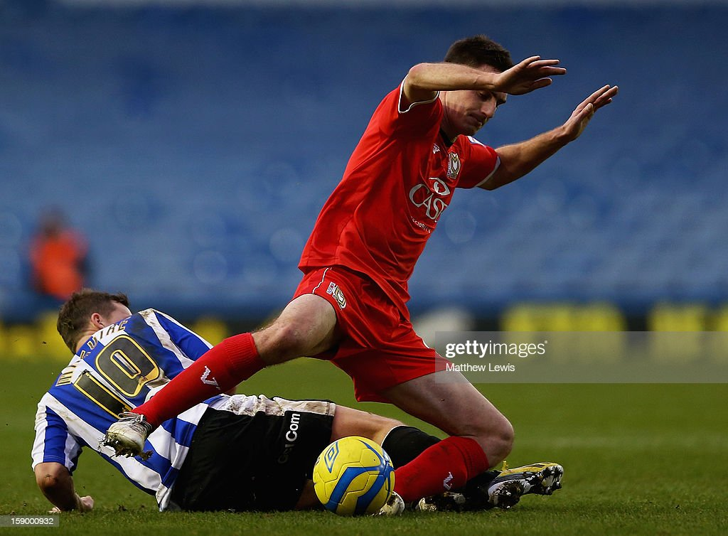 Darren Potter of Milton Keynes Dons is tackled by Chris Maguire of Sheffield during the FA Cup with Budweiser Third Round match between Sheffield Wednesday and Milton Keynes Dons at Hillsborough Stadium on January 5, 2013 in Sheffield, England.