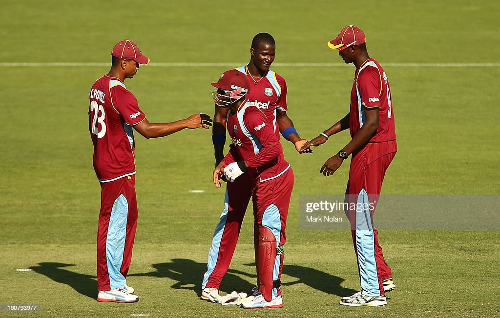 Darren Sammy and Devon Thomas of the West Indies celebrate the wicket of Phillip Hughes of Australia during the Commonwealth Bank One Day International Series between Australia and the West Indies at Manuka Oval on February 6, 2013 in Canberra, Australia.