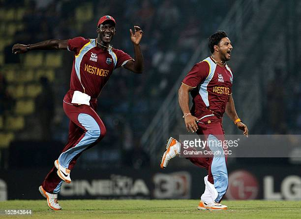 Darren Sammy and Ravi Rampaul of West Indies celebrate the wicket of Luke Wright of England during the A1 versus B2 Super Eight match between England...