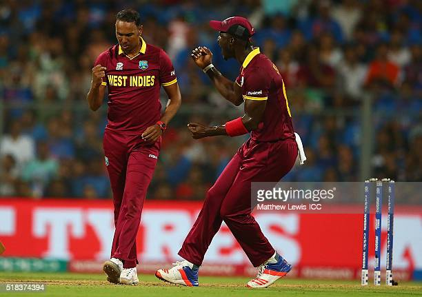 Darren Sammy Captain of the West Indies congratulates Samuel Badree of the West Indies on the bowling Rohit Sharma of India LBW during the ICC World...