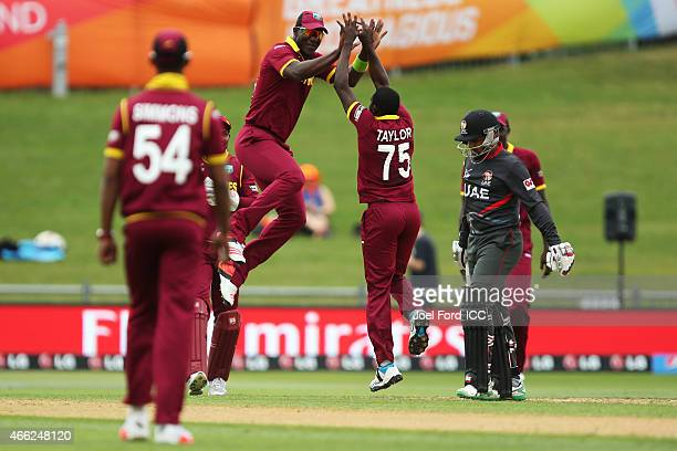 Darren Sammy celebrates with Jerome Taylor of the West Indies after Taylor bowled out Khurram Khan of the UAE during the 2015 ICC Cricket World Cup...
