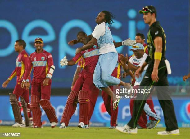 Darren Sammy of the West Indies is congratulated by Chris Gayle and the rest of his teammates after hitting the winning runs as Mitchell Starc of...