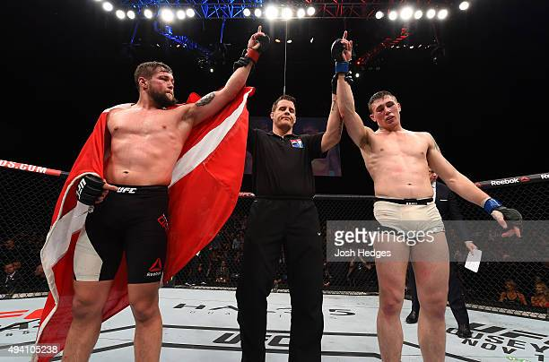 Darren Till and Nicolas Dalby raise their hands as the judges give them a draw in their welterweight fight during the UFC event at 3Arena on October...